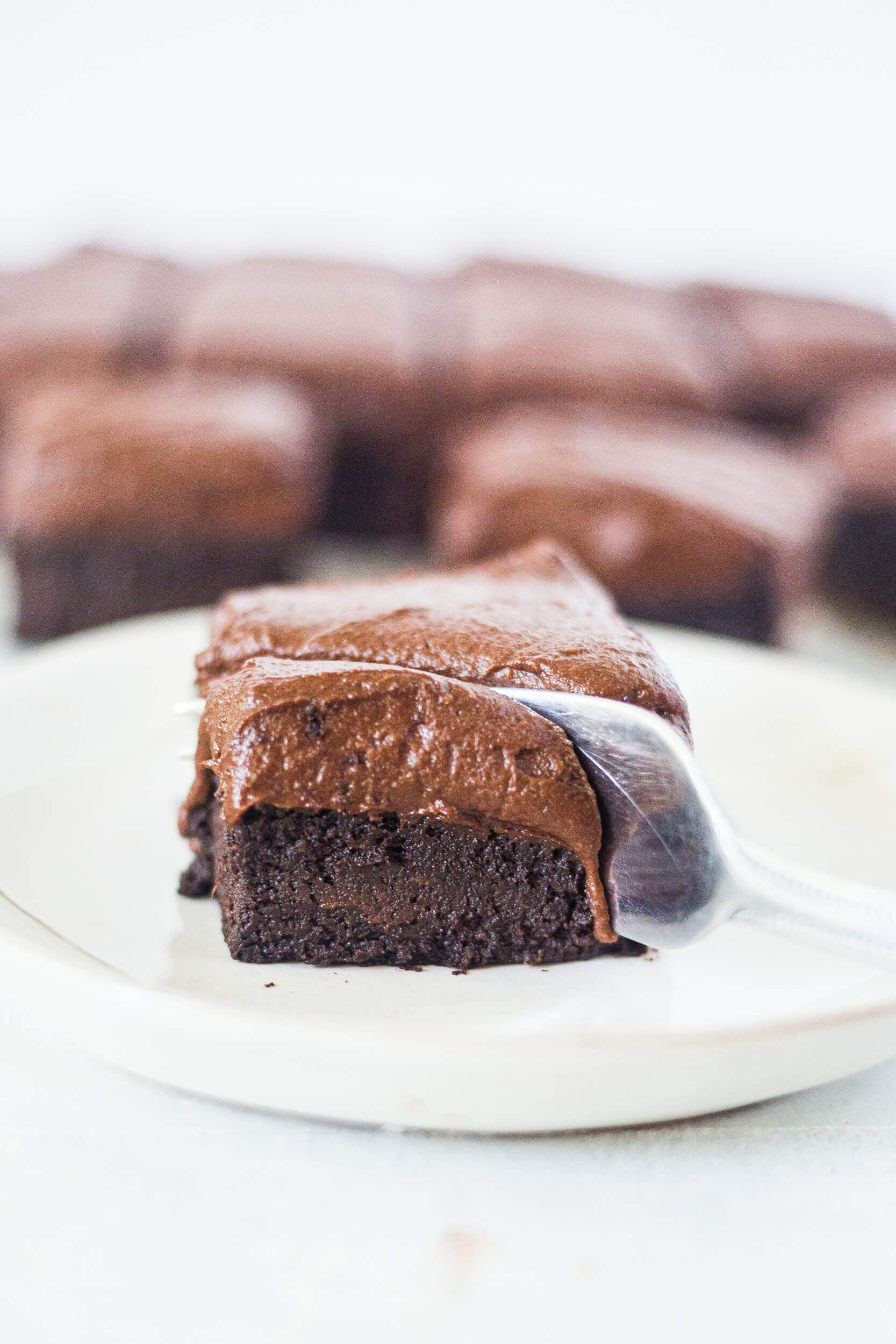 fork cutting into sweet potato cake with chocolate frosting