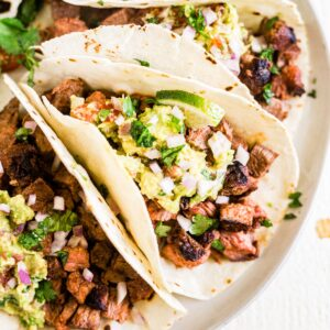 three carne asada tacos on a white plate topped with fresh guacamole, lime and cilantro