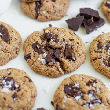 coconut flour chocolate chip cookies on parchement paper with melted chocolate and sea salt