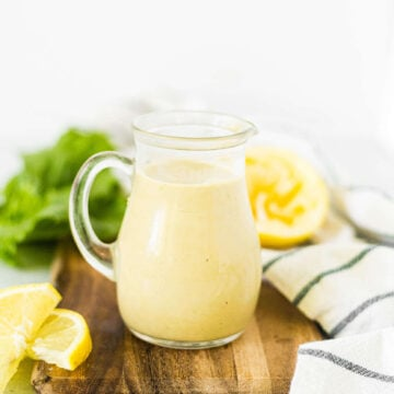 vegan caesar dressing recipe in a glass jar on a wooden cutting board