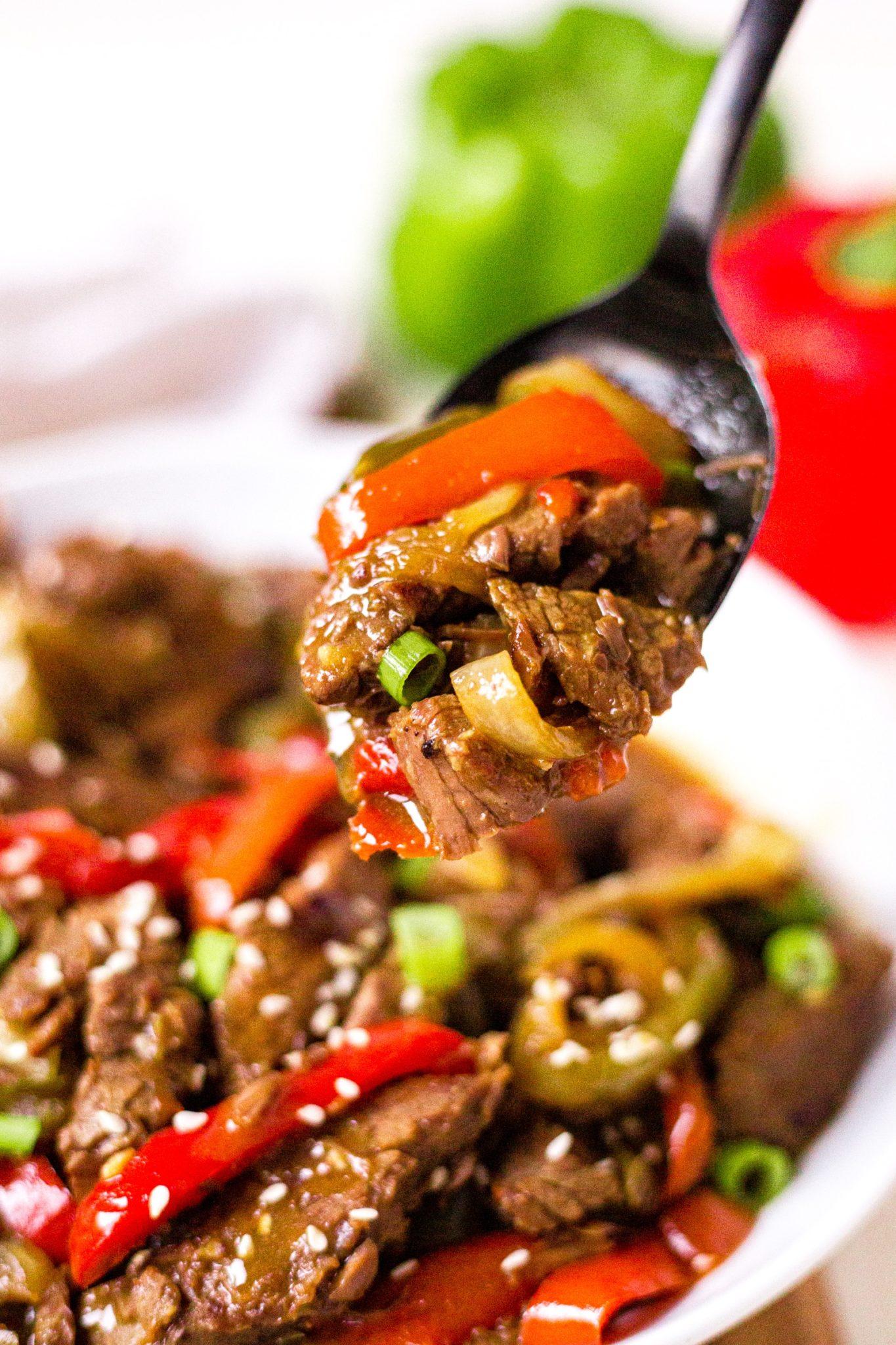 black serving spoon serving out crockpot pepper steak