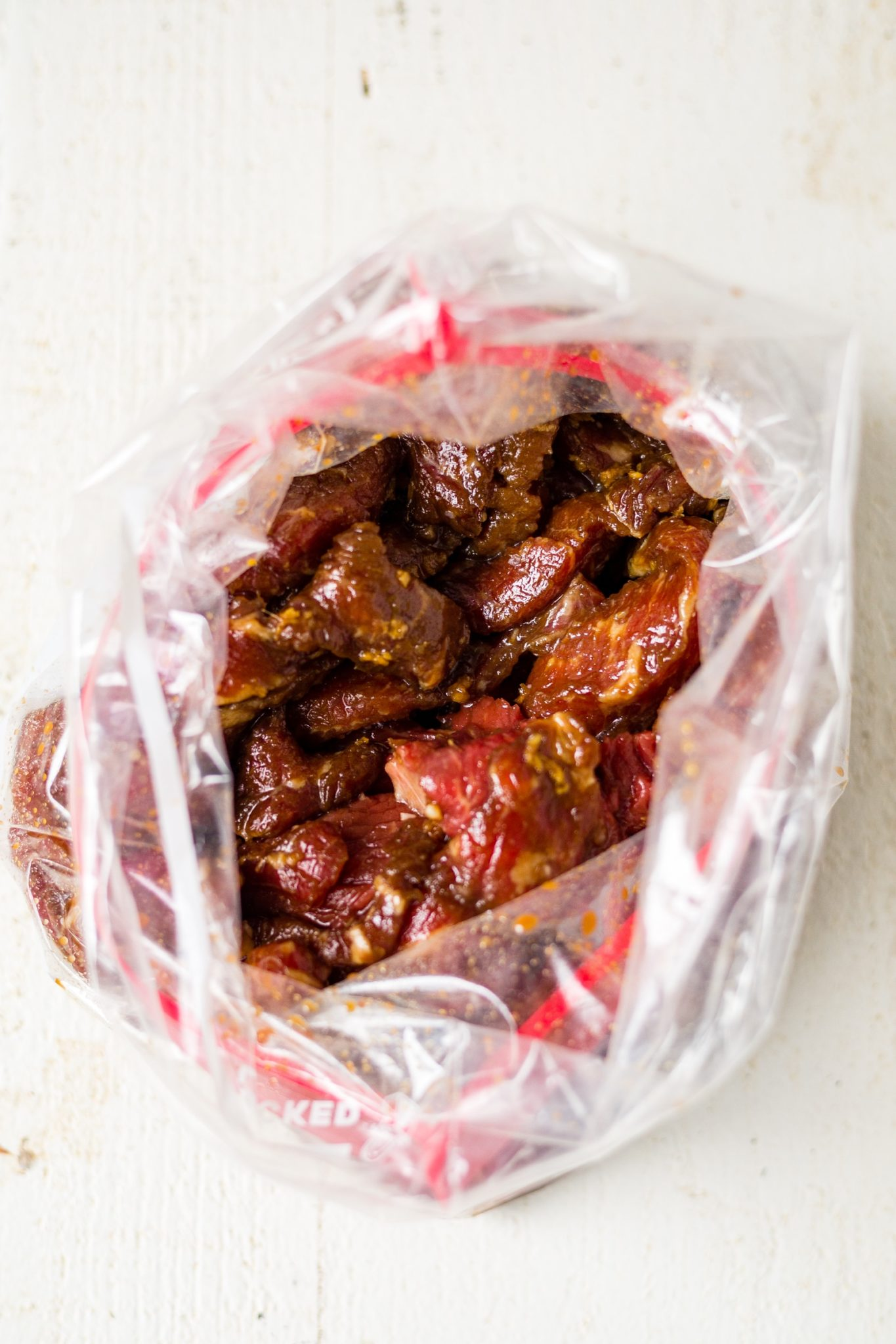 sirloin steak marinating in a freezer bag with soy sauce, ginger and garlic