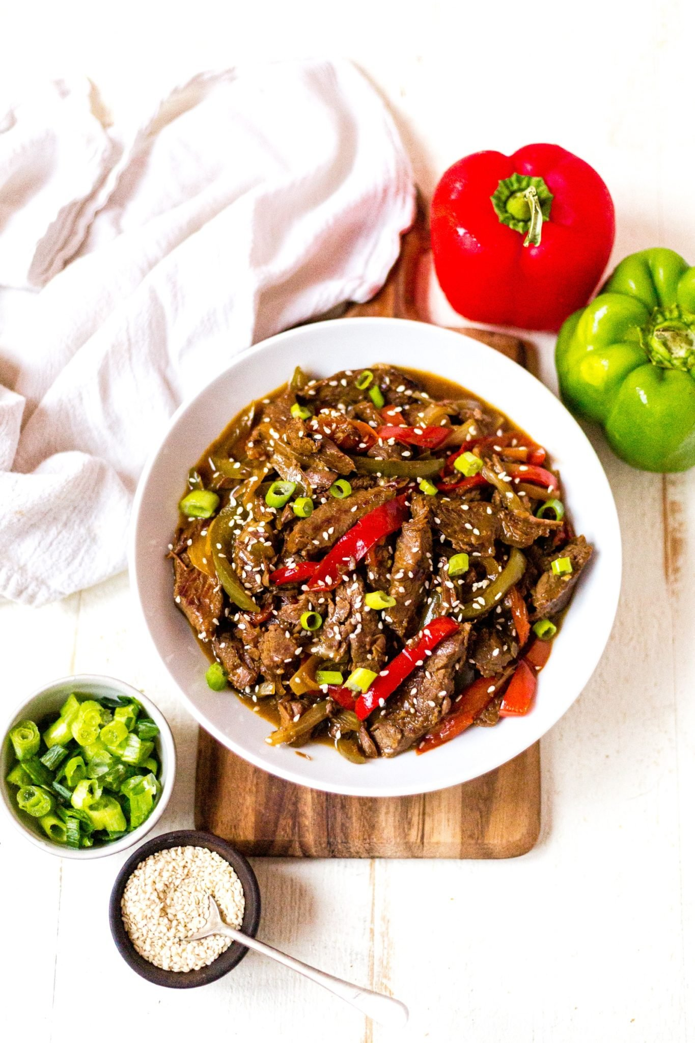crockpot pepper steak in a white bowl topped with sesame and green onion