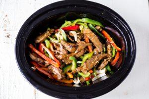 pepper steak ingredients in a crock pot before cooking
