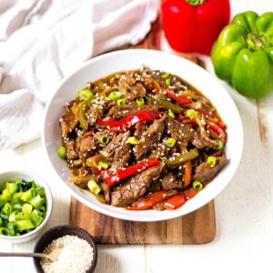 crockpot pepper steak in a white bowl with sesame seeds and green onion