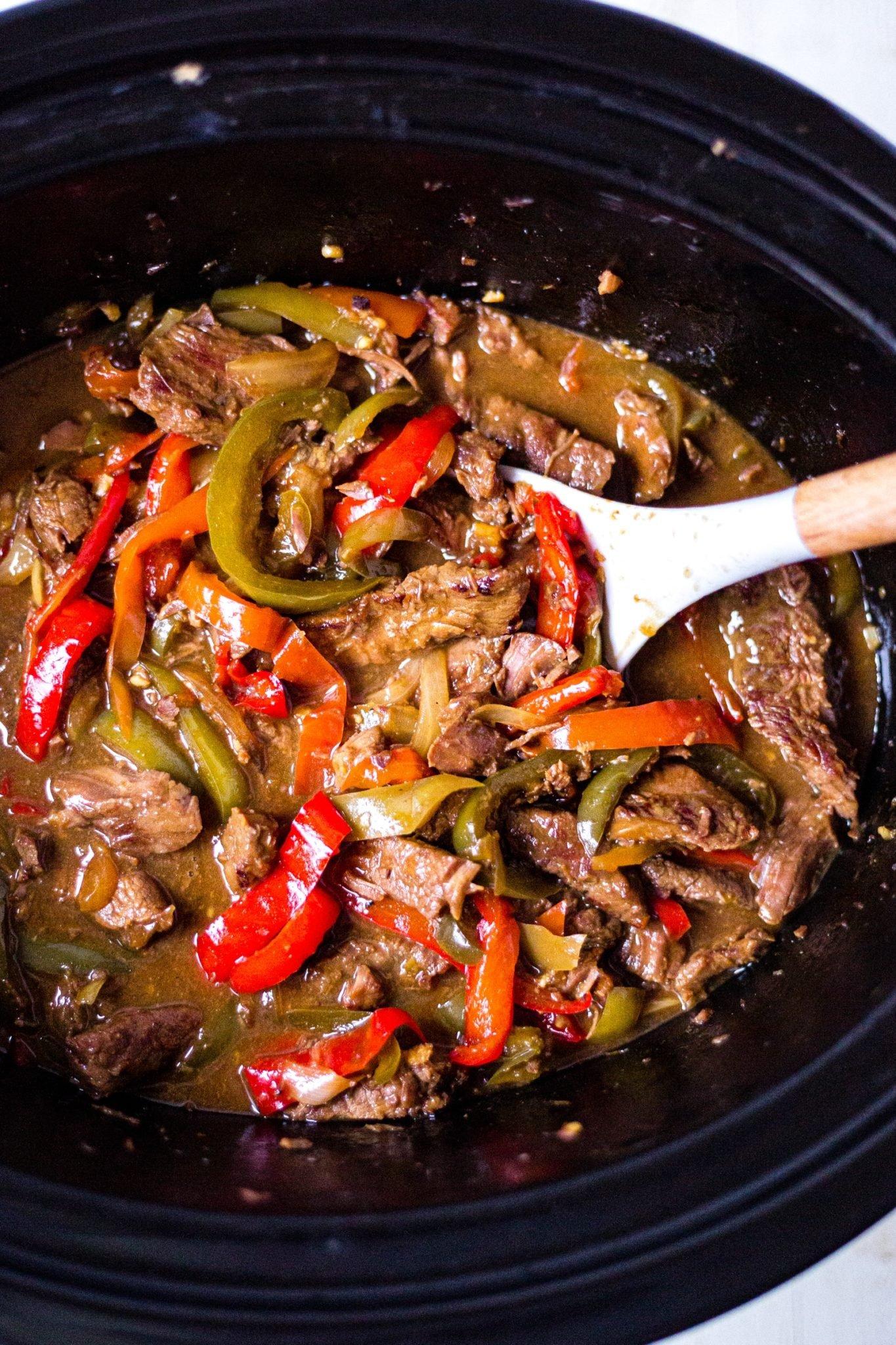pepper steak recipe in the crockpot with a serving spoon