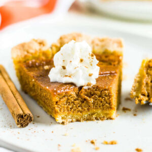 dairy free pumpkin pie on a white plate with a bite taken out of one