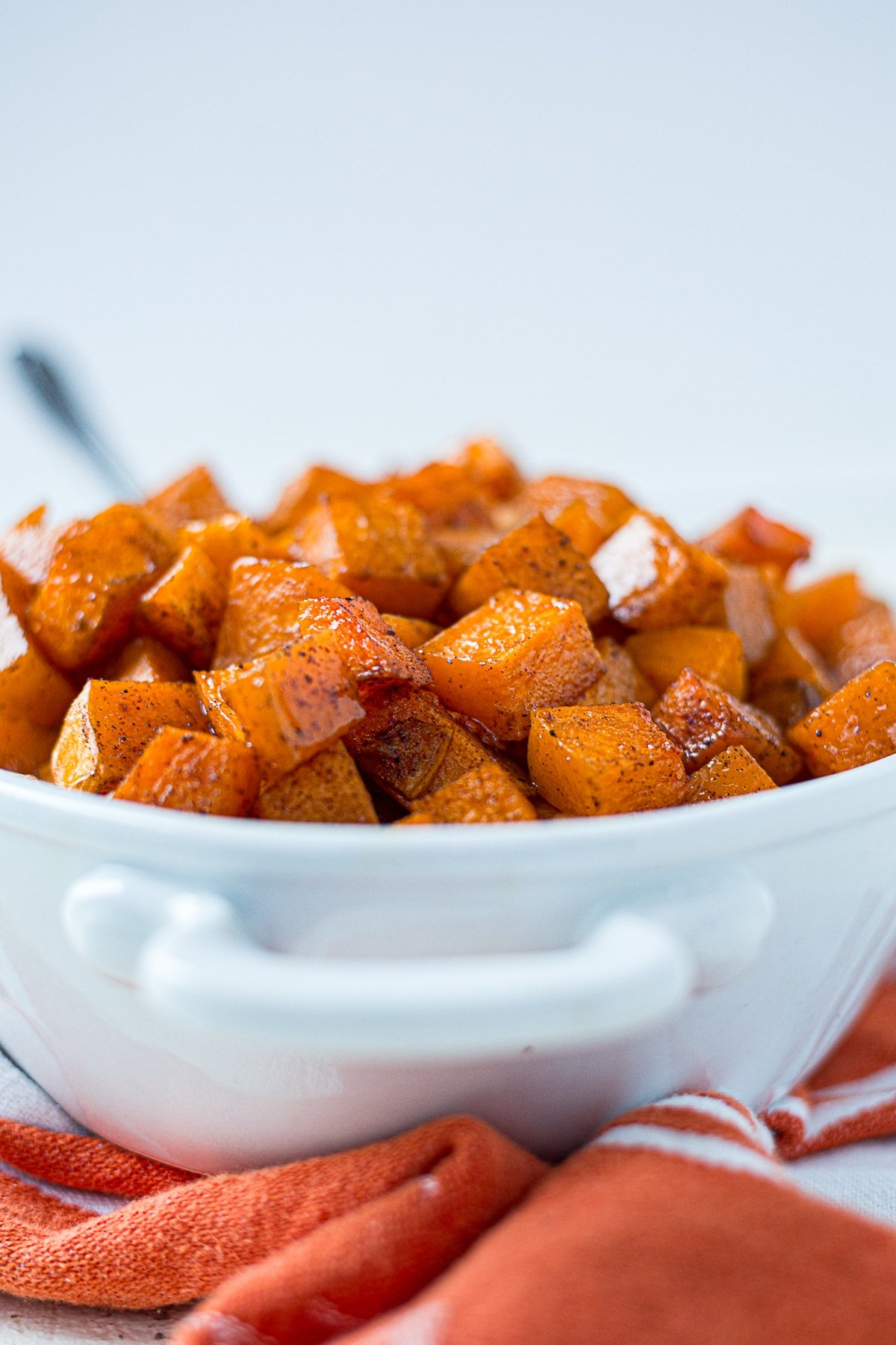 Roasted butternut squash cooked with cinnamon and maple syrup piled  high in a white bowl