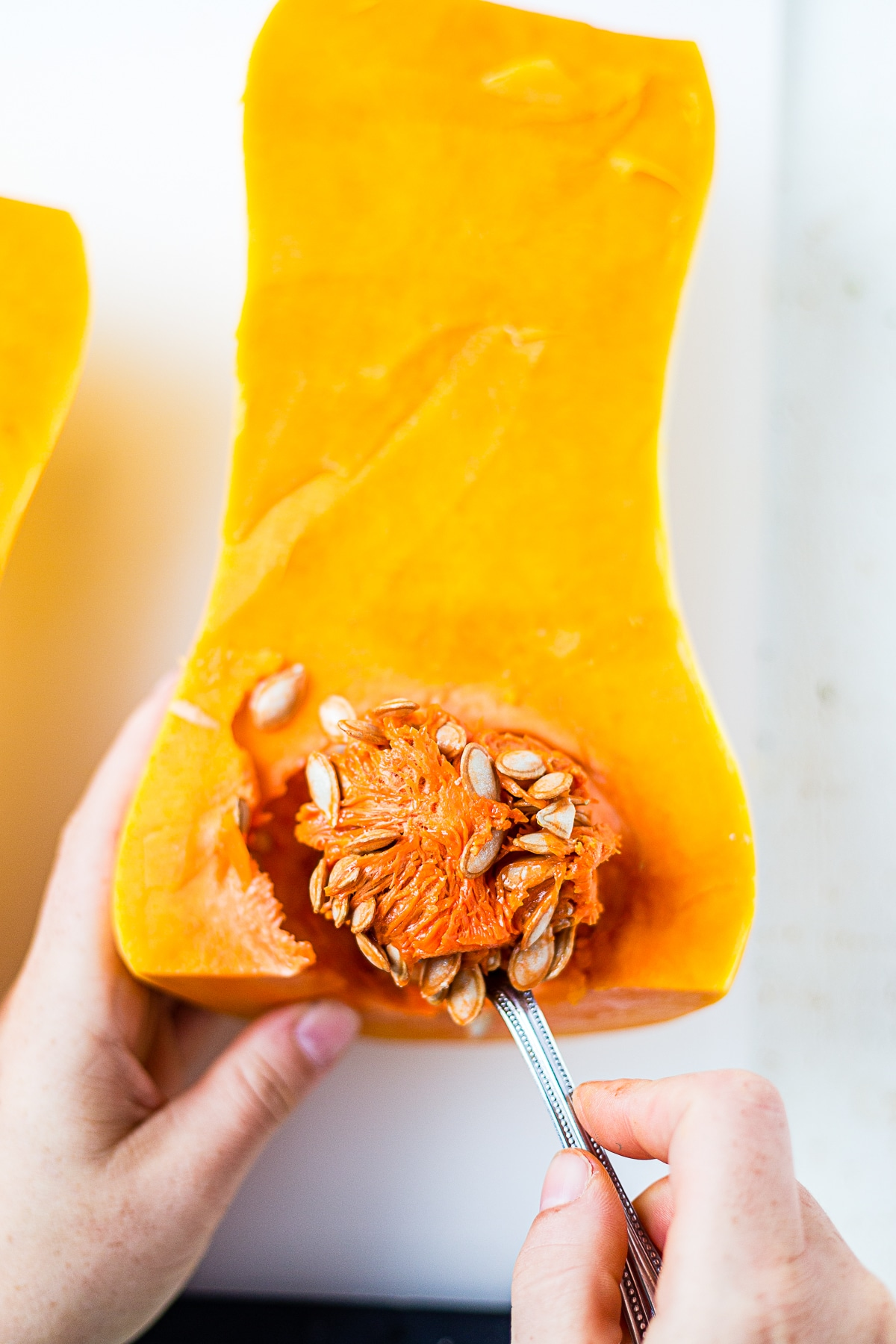 hand scooping out the seeds of a butternut squash