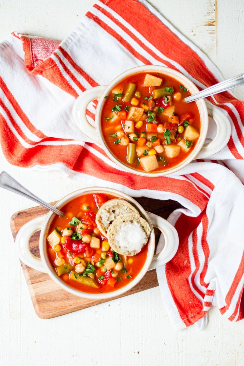 two bowls of homemade vegetable soup on a wood board with a white and orange towel and spoons