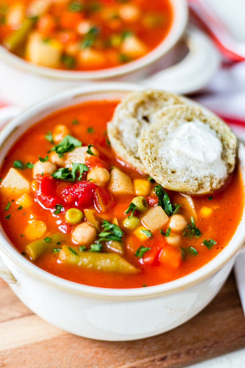 vegetable soup in a white bowl with a buttered roll on the side