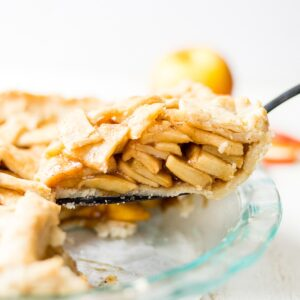 gluten free apple pie slice being pulled out of a glass baking dish