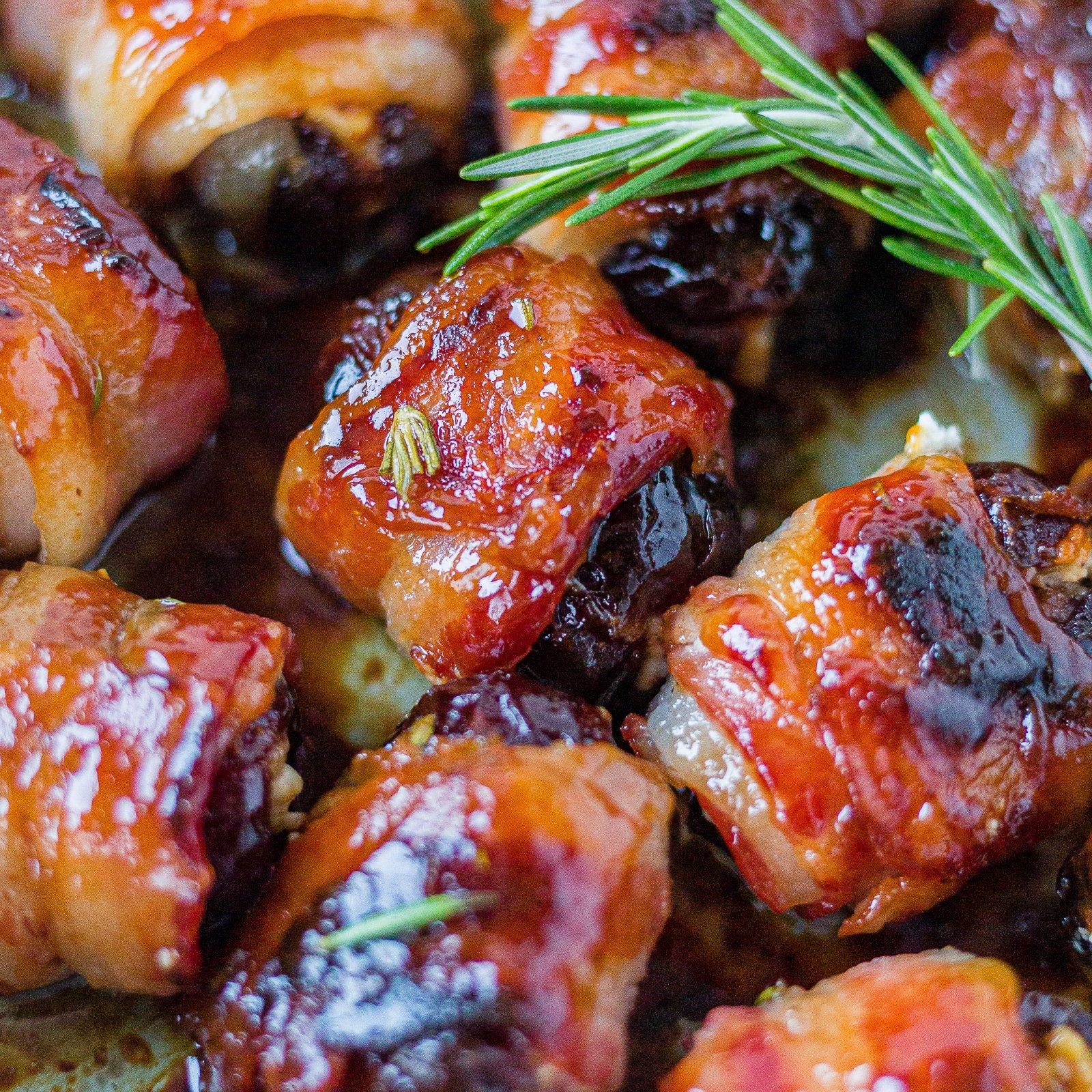 bacon wrapped dates in a pan with honey glaze and rosemary