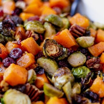 roasted brussel sprouts and butternut squash in a serving dish with pecans and cranberries