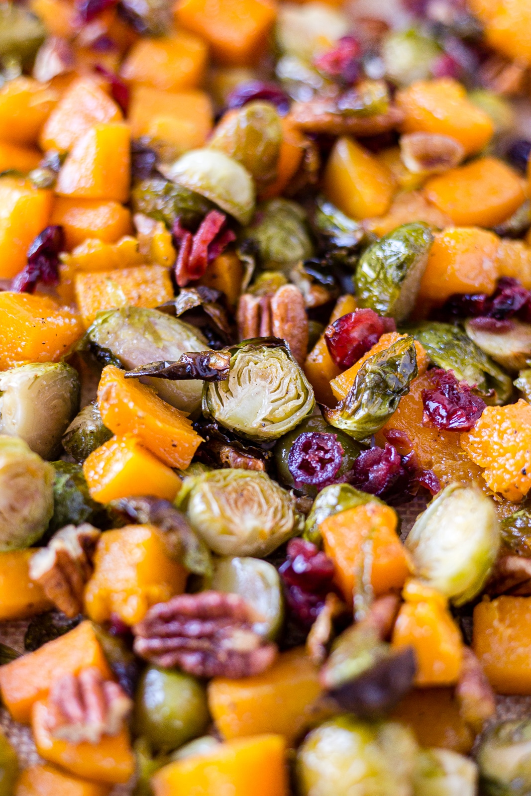 brussel sprouts and butternut squash roasted on a sheet pan with pecans and cranberries