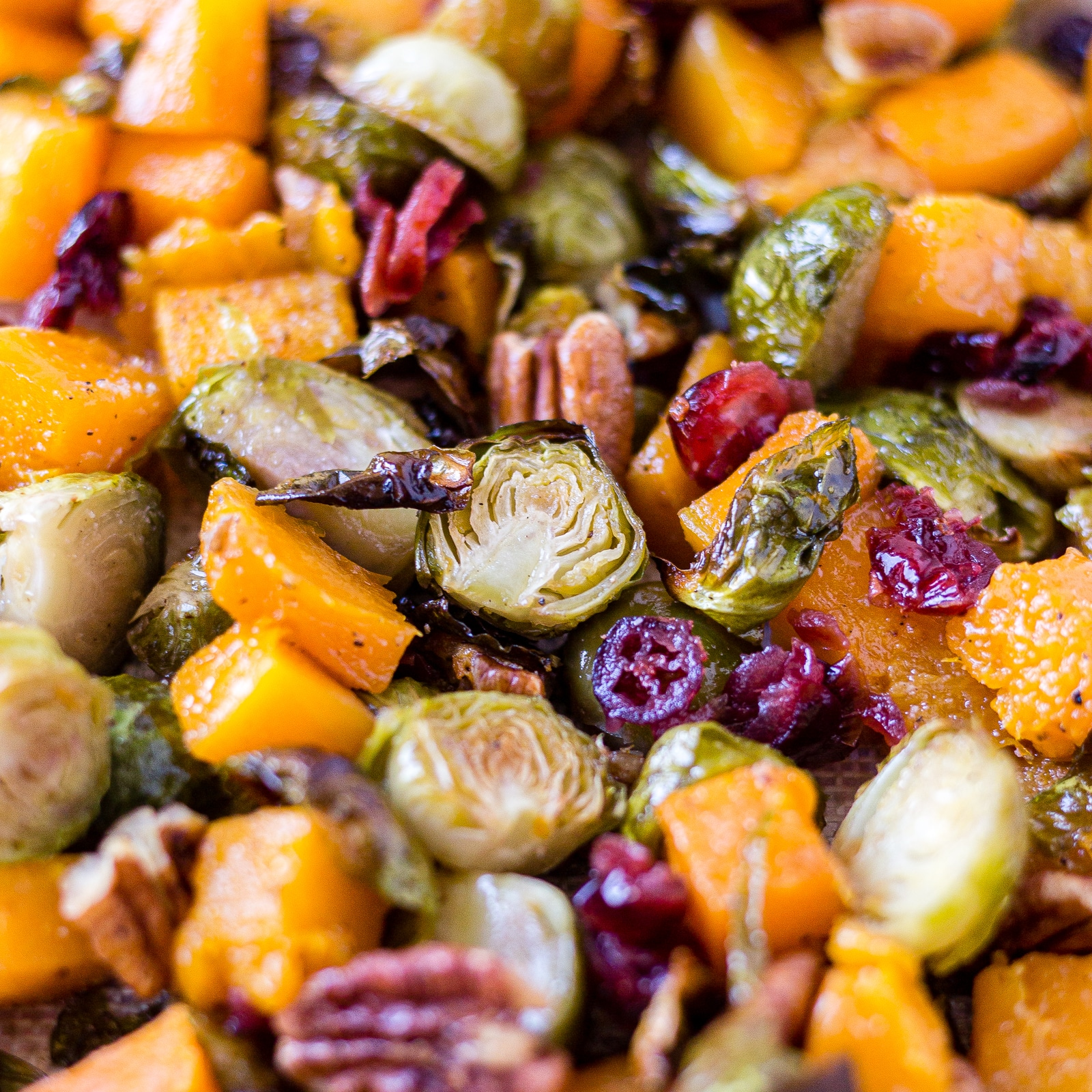 brussel sprouts and butternut squash on a sheet pan with pecans and cranberries