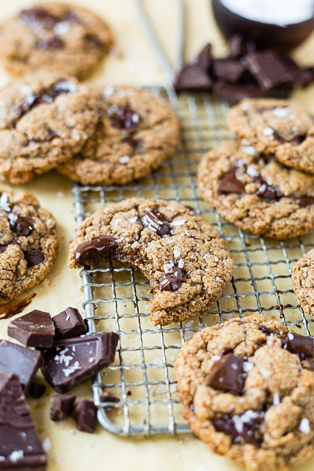 almond butter cookies on a piece of parchment paper with chocolate chunks and sea salt