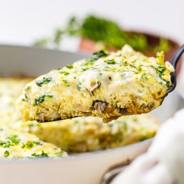 a piece of vegetable frittata being pulled out of the pan