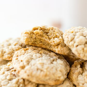 a stack of brown butter oatmeal cookies and the top one has a bite taken out