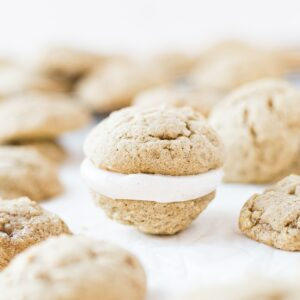 chai whoope pie with cinnamon frosting on a piece of parchment paper surrounded by other cookies