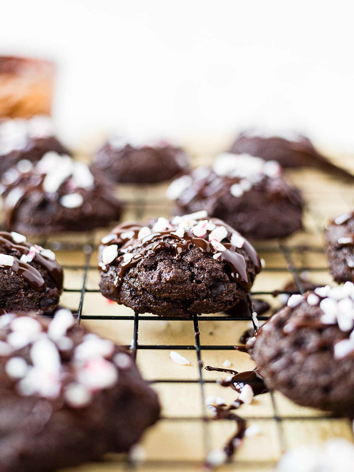 paleo double chocolate peppermint cookie on a wire rack cooling with melted chocolate and crushed peppermint