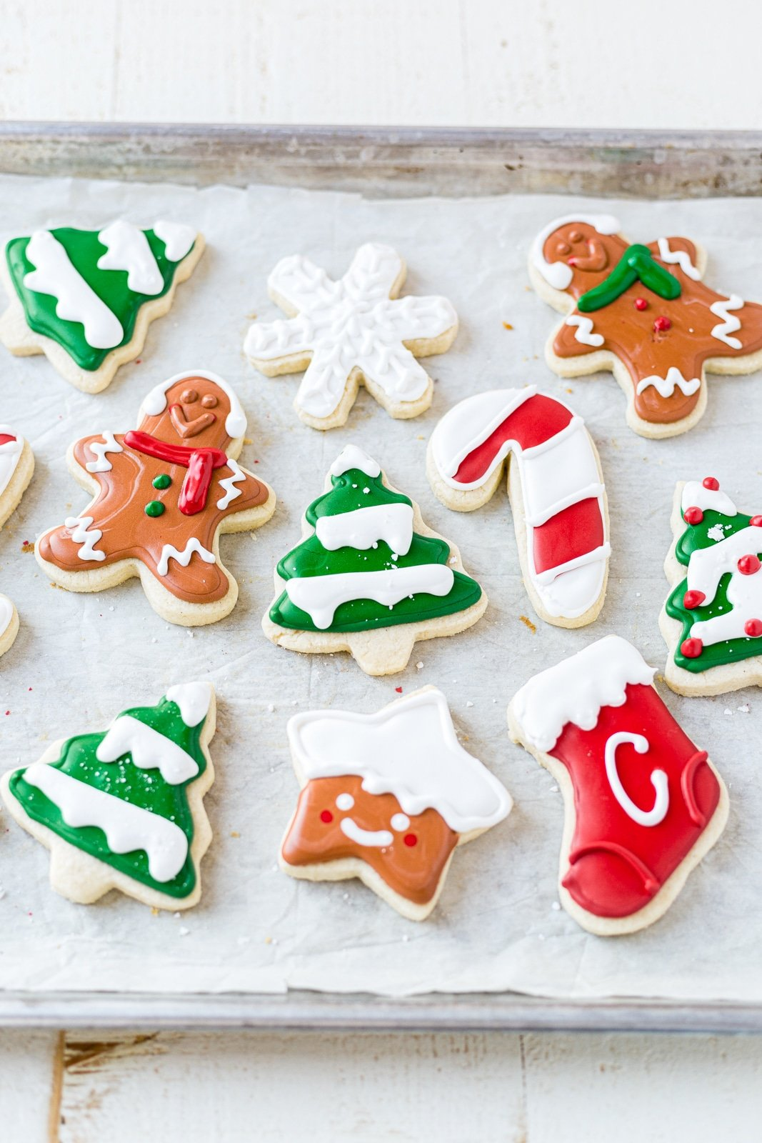 10 gluten free sugar cookies on a baking sheet decorated for christmas with royal icing