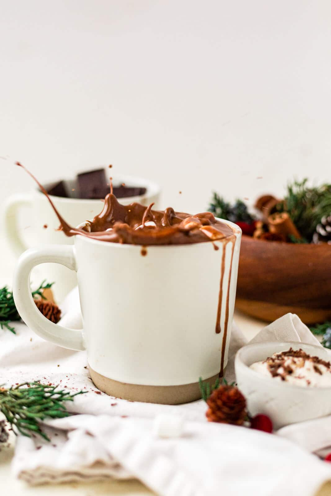 hot chocolate splashing out of the mug while a mini marshmallow is dropped into it