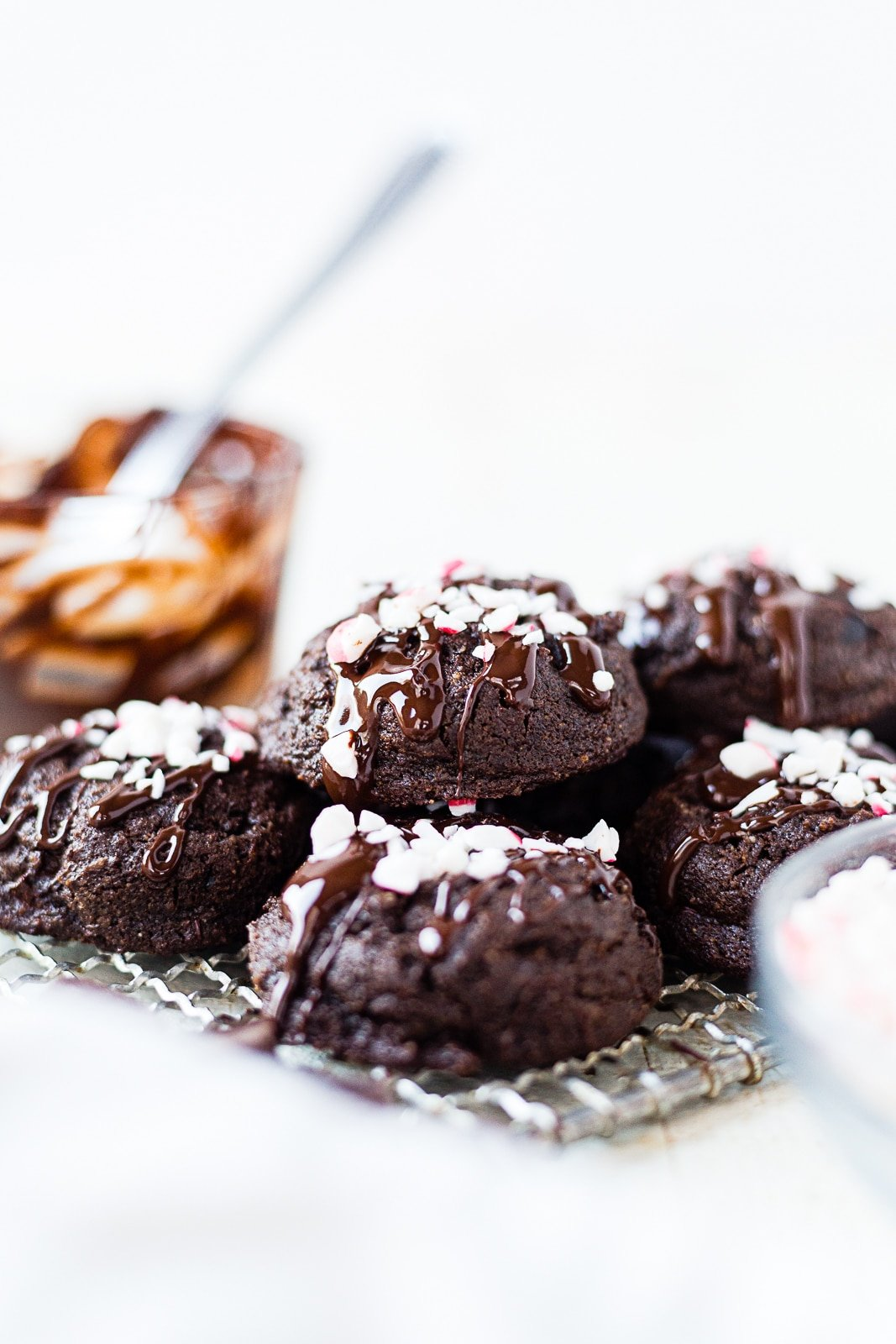 double chocolate peppermint cookies on a wire rack with melted chocolate and peppermint