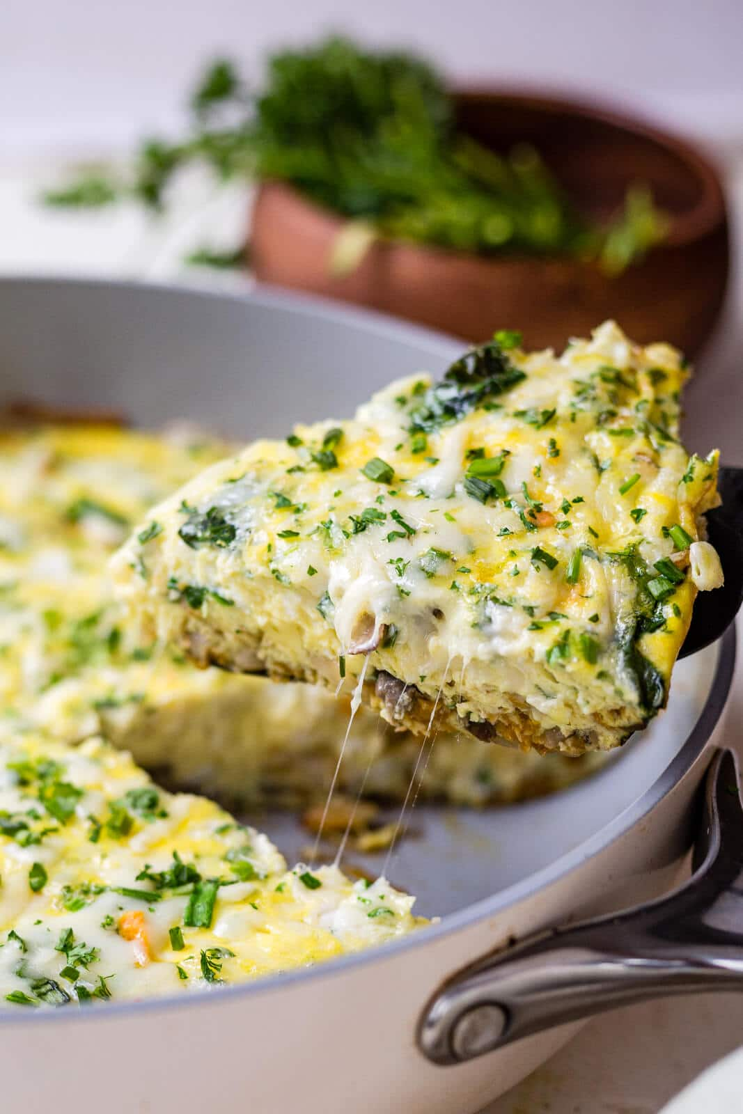 a piece of vegetable frittata being pulled out of the pan with a string of cheese coming off and its topped with fresh herbs