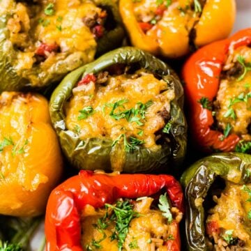 overhead shot of air fryer stuffed peppers topped with melted cheddar cheese and chopped parsley