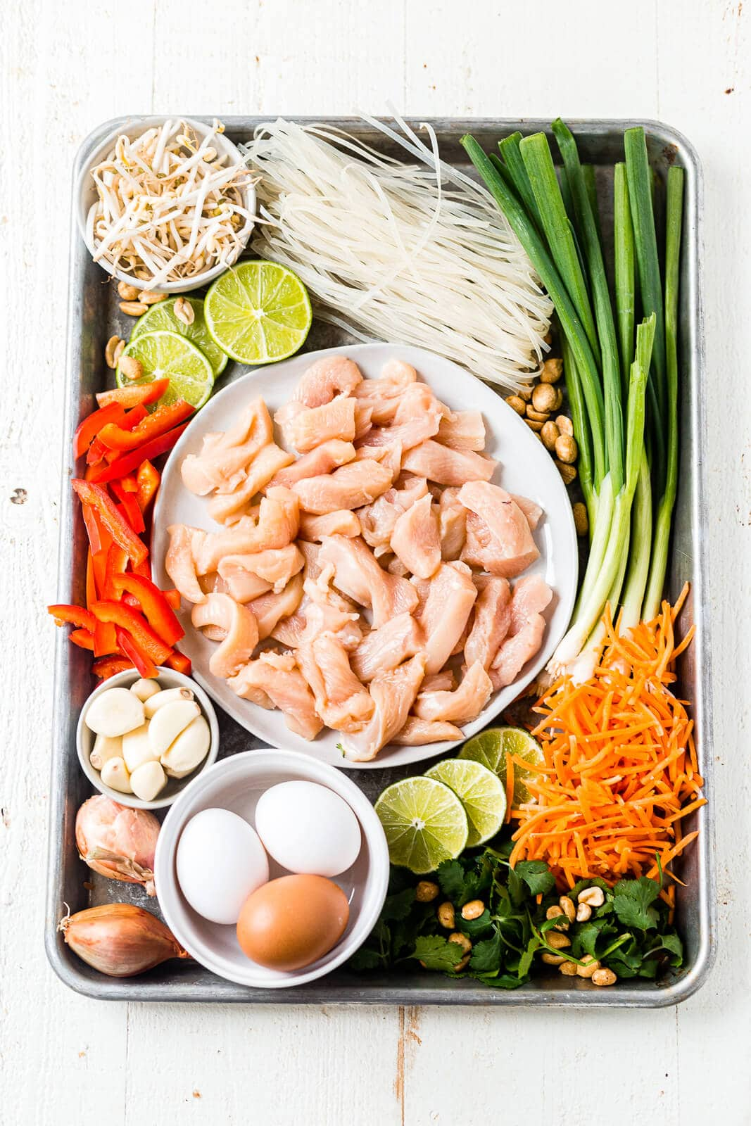 all of the ingredients for healthy chicken pad thai arranged on a sheet pan