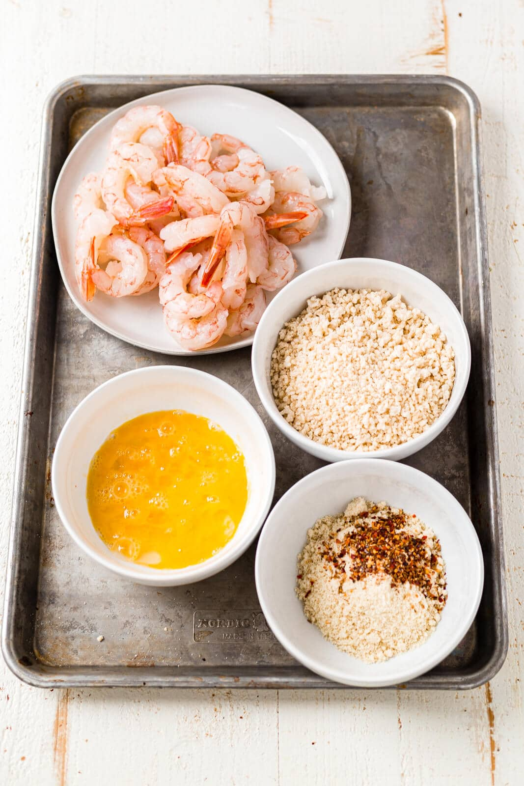 all of the ingredients for breaded shrimp in the air fryer shrimp sitting on a sheet pan before being breaded and cooked