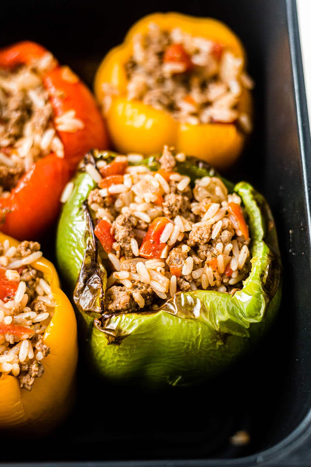air fryer stuffed peppers in the basket with charred edges right before being topped with cheese