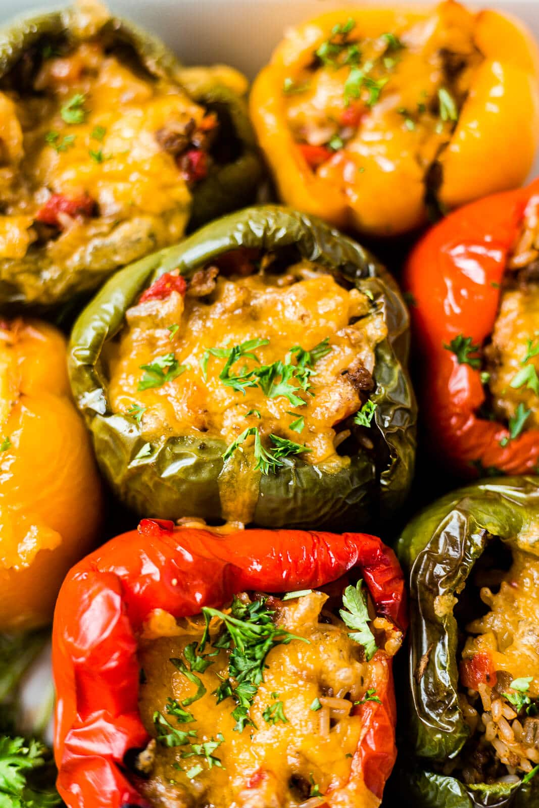 close up shot of air fryer stuffed peppers topped with cheese and parsley