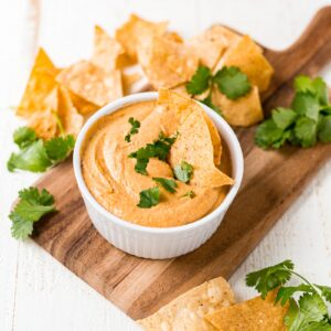 vegan cashew queso in a white dish topped with chopped cilantro