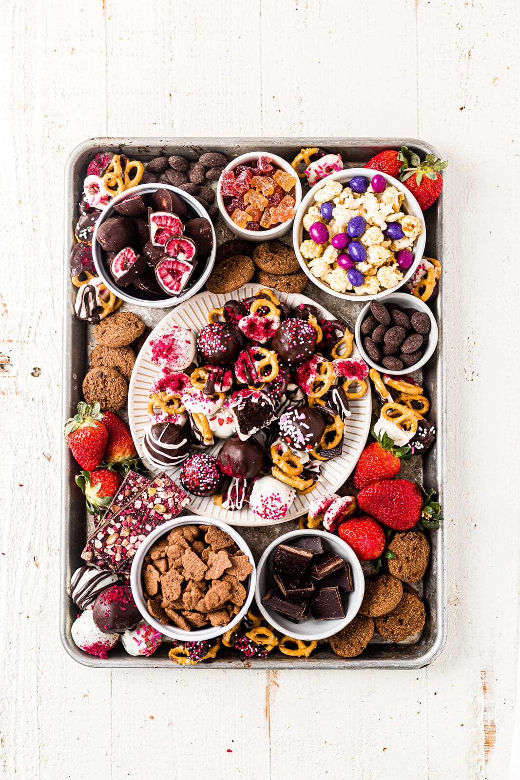 a healthy valentines'd day dessert board full of chocolate covered fruit, pretzels, nuts, popcorn and cookies