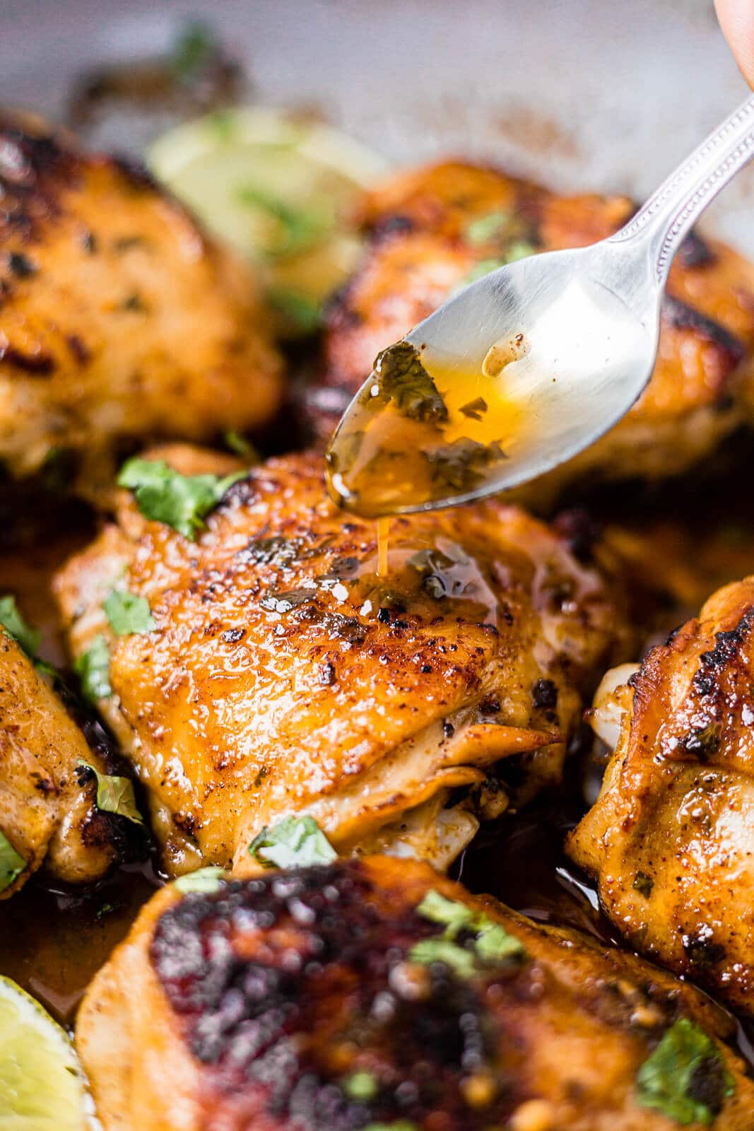 a spoon drizzling sauce over cilantro lime chicken thighs