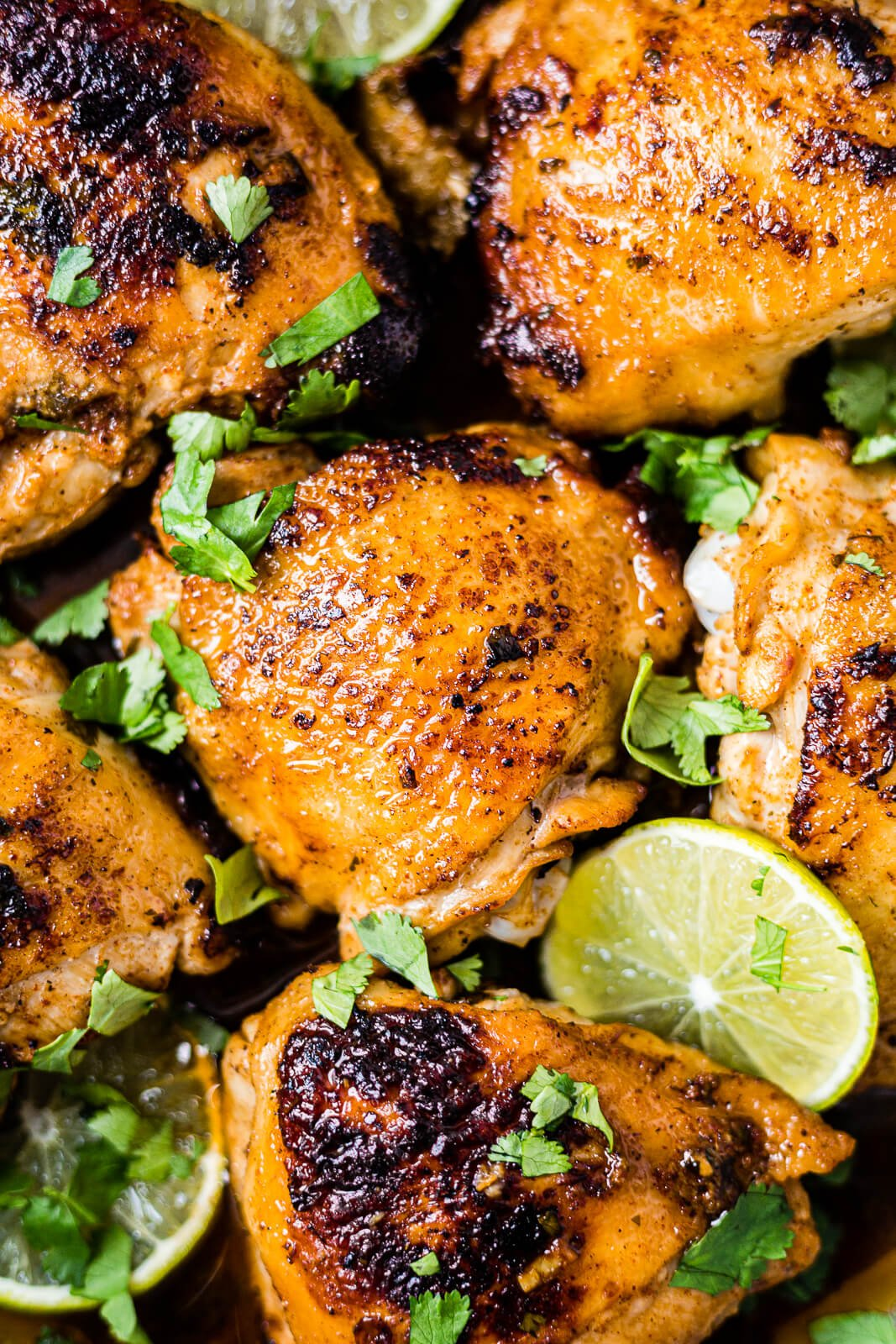 6 pieces of cilantro lime chicken thighs in a skillet with fresh cilantro and lime wedges