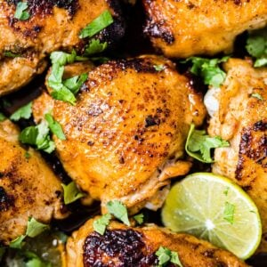 crispy cilantro lime chicken in a oven safe pan with fresh cilantro and lime slices