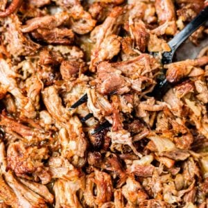 a black fork scooping out crispy instant pot carnitas from a sheet pan