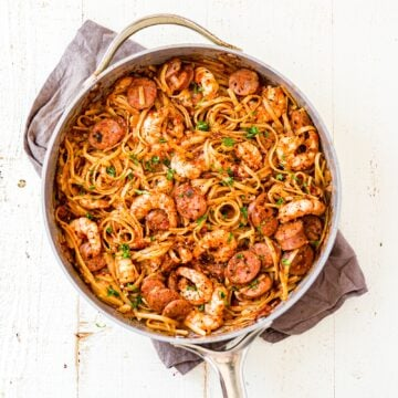 a large skillet filled with creamy cajun shrimp pasta topped with pasta