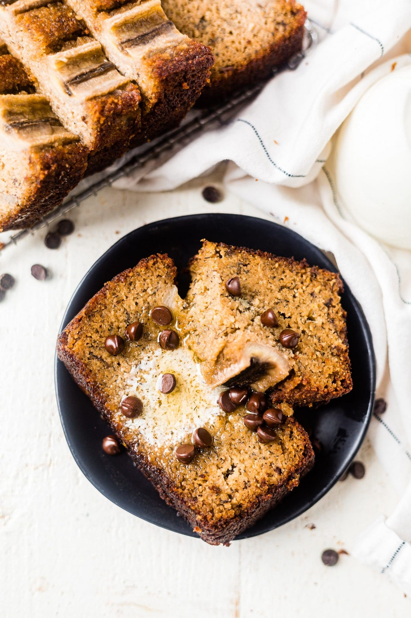 two pieces of almond flour banana bread on a black dessert plate topped with melted butter and chocolate chips