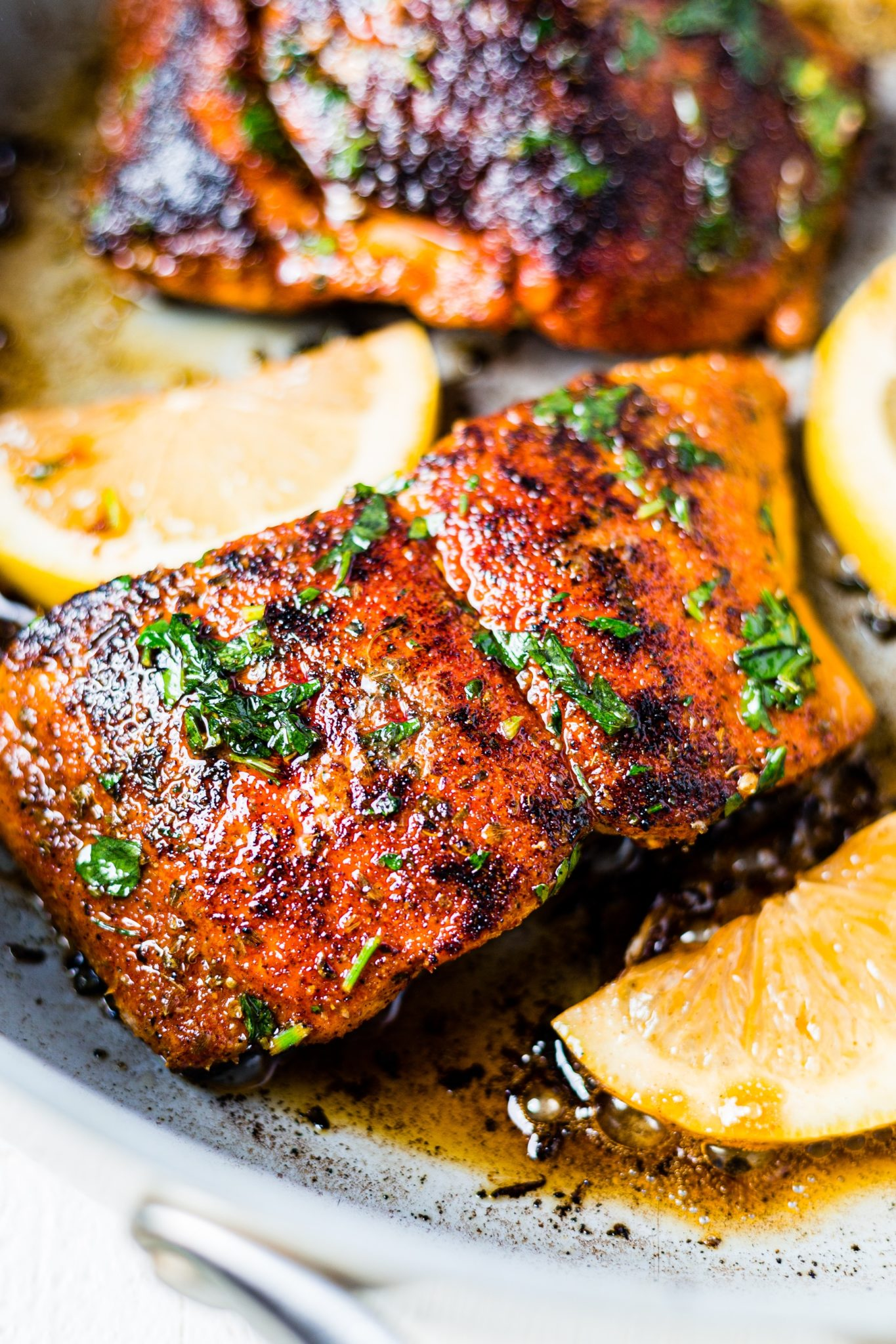 a piece of blackened salmon in a skillet with lemon wedges and topped with chopped parshley