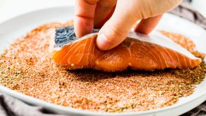 a hand dipping salmon filet into a mix of blackened seasoning