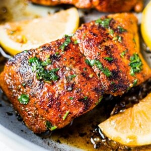 blackened salmon in a skillet with avocado oil and lemon and topped with fresh parsley