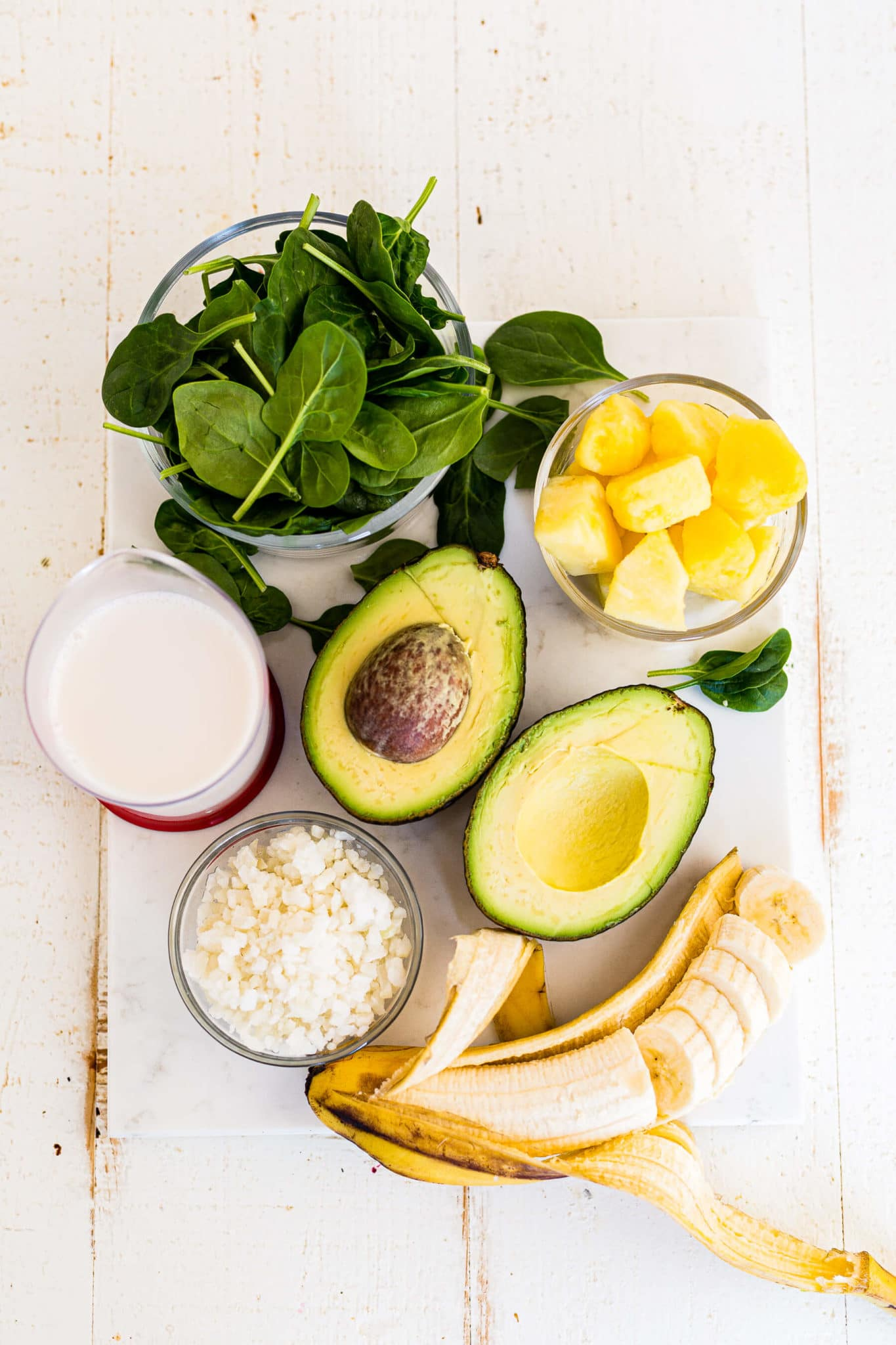 banana, avocado, pinapple, almond milk and spinach on a white table