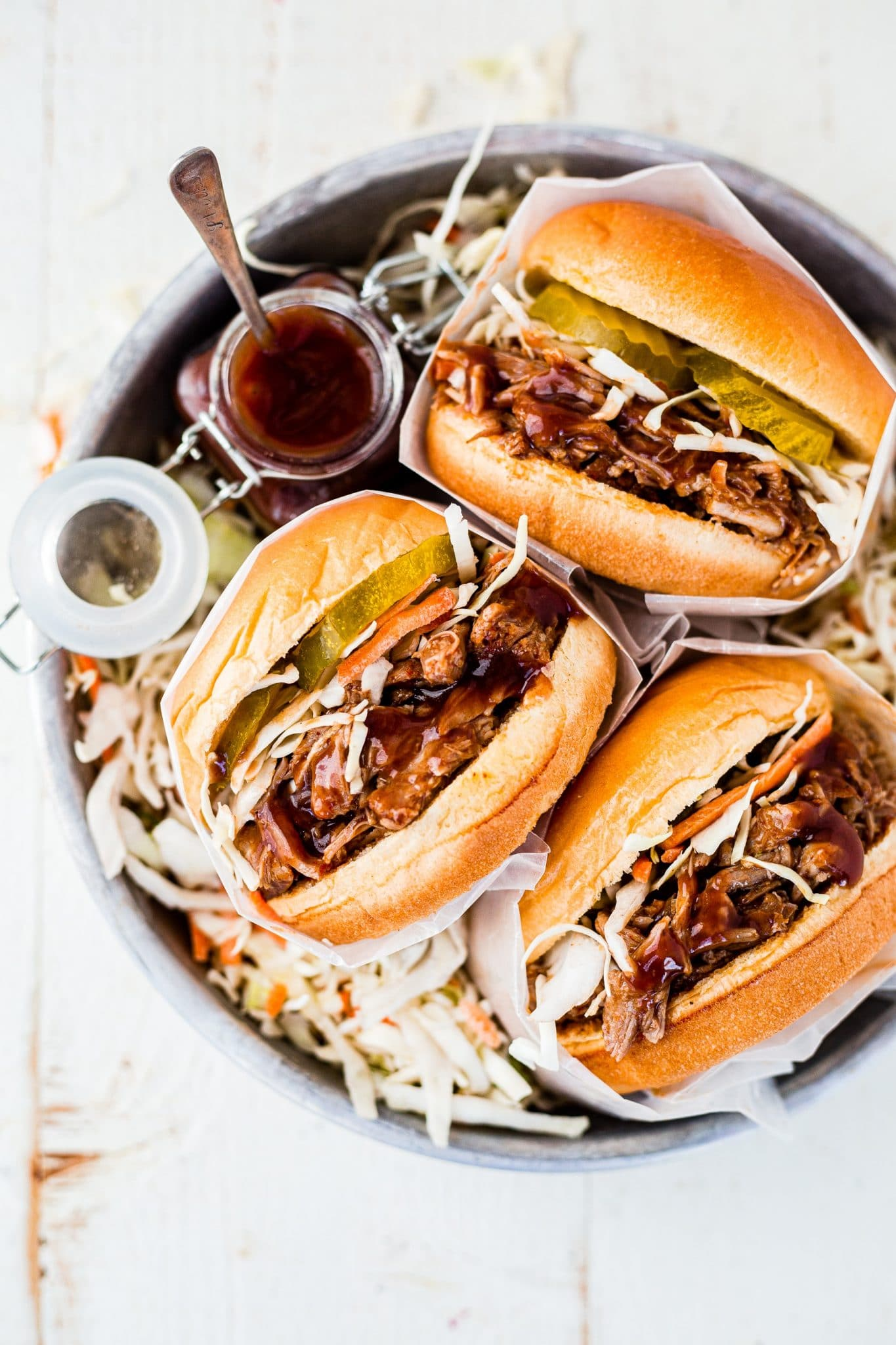3 instant pot pulled pork sandwiches topped with coleslaw and pickles on a serving tray with extra bbq sauce