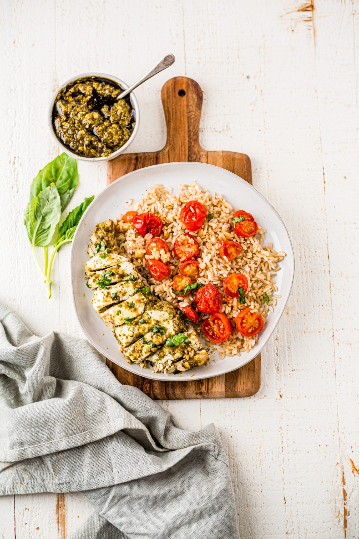 pesto chicken topped with mozzarella on a white plate served with brown rice and garlic roasted tomatoes