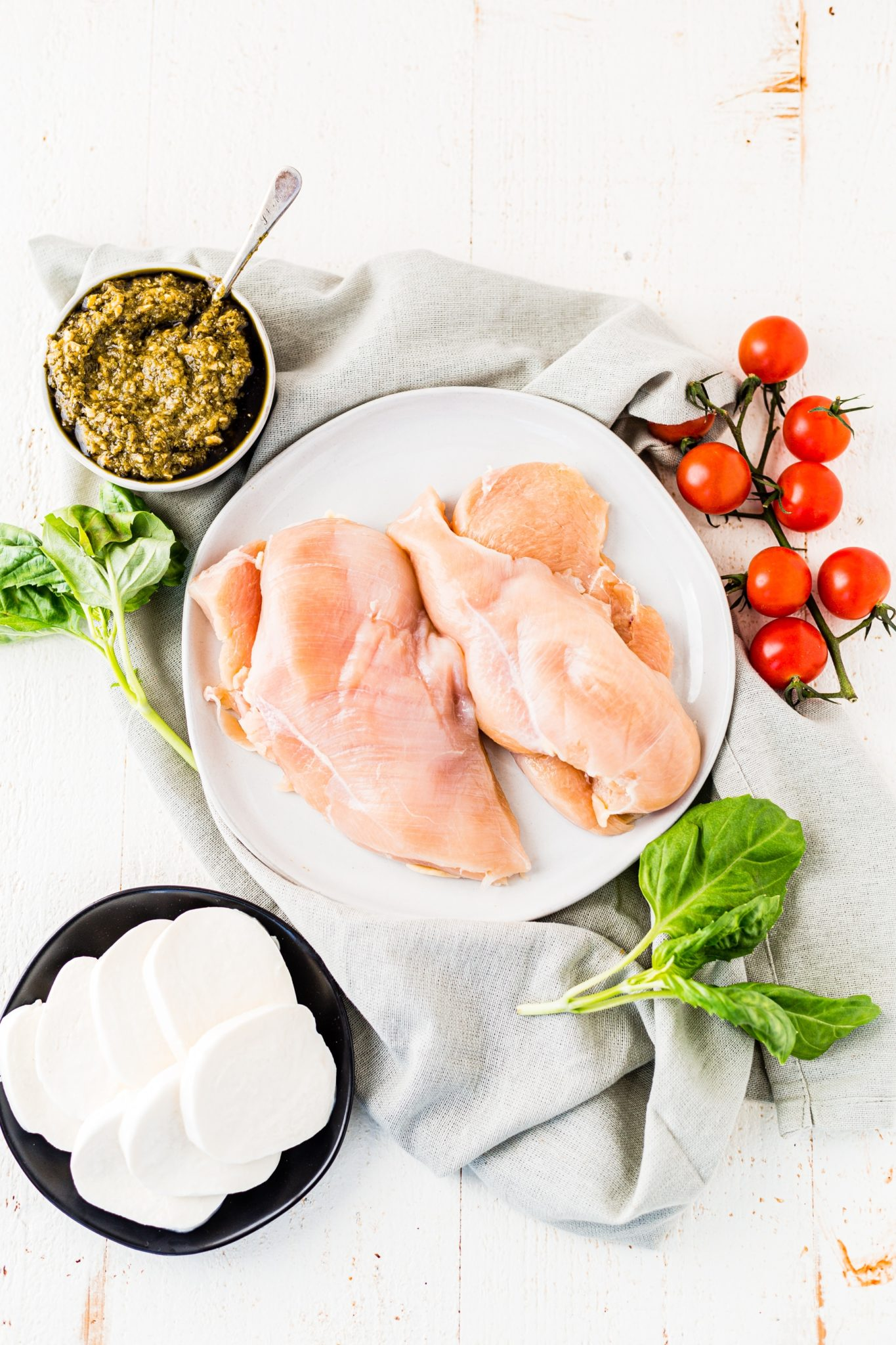 ingredients for pesto chicken on a white table