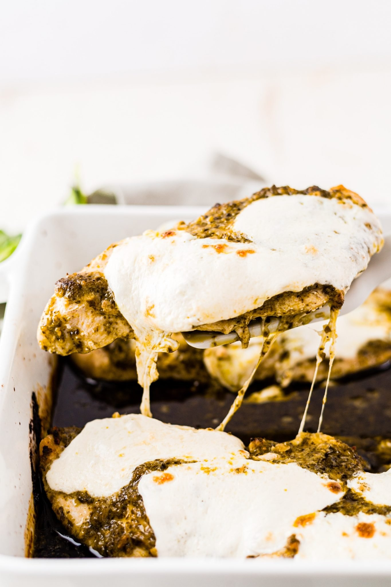 pesto chicken covered in mozzarella being pulled out of a baking dish and the cheese